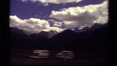1979: mountain skyline behind a highway where vehicles are moving along  Stock Footage