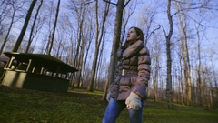 Woman walk through park with sun shining on face skin side shot 4K Stock Footage