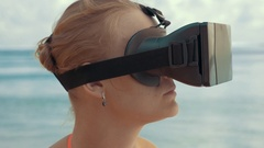 Woman entertaining with VR glasses on the beach Stock Footage