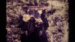1979: tourists enjoying seeing water cascading down a steep cliff from a bridge Stock Footage