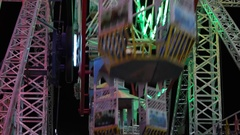 Close up of carnival lights, ferris wheel, giant rides in an amusement park Stock Footage