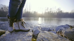 Person in warm white winter boots stand on a rock near river 4K Stock Footage