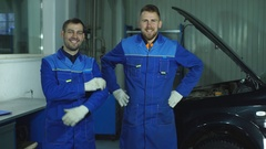 Two satisfied car mechanics look at the camera Stock Footage