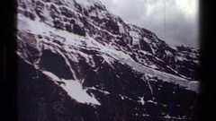 1979: snow clings to the surface and in the cracks on a mountain  Stock Footage