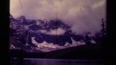 1979: enormous snow-capped mountains enveloped in clouds surround a lake CANADA Stock Footage