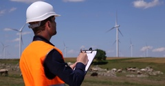 Electricity Engineer Man Taking Notes on Wind Turbine Activity Using Clipboard Stock Footage