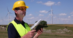 Alternative Energy Worker Man Using Digital Tablet Device Looking Wind Turbines Stock Footage