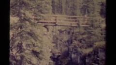 1979: people cross a wooden log bridge high above a ravine CANADA Stock Footage