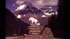 1979: a wooden sign beside a road: mount robson park with jagged alpine-like Stock Footage