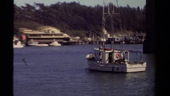 1980: trawler sails under a freeway bridge on a calm day at a mooring area  Stock Footage