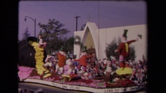 1967: a parade float features irish characters as it moves down a street lined Stock Footage