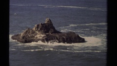 1980: waves gather around sandstone cliff in otherwise calm waters MENDOCINO Stock Footage