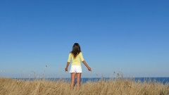 4K. Woman in yellow blouse have lift hands against sea. Approach of focus Stock Footage