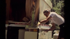 1980: an older man is lowering a tarp by spinning a hand crank MENDOCINO Stock Footage