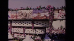 1967: float with images of historic monuments slowly moves down, people ride Stock Footage
