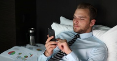 Business Male Searching Internet on Mobile Phone Comfortable Bed Inside Bedroom Stock Footage