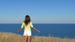 4K. Woman in yellow blouse have lift hands against sea.  Stock Footage