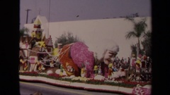 1967: people watch as a float carrying santa's image heads down a street Stock Footage