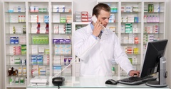 Experienced Pharmacist Man Talking Landline Telephone with Client Pharmacy Shop Stock Footage