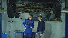 Mechanic with clipboard talking to man or owner at car shop Arkistovideo