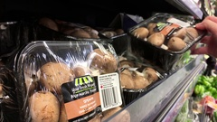 Woman's hand picking whole mushrooms inside Walmart store Stock Footage