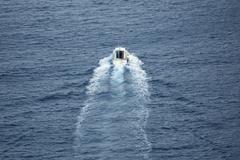 Small boat navigating, rear view, long shot Stock Photos