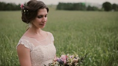Beautiful bride standing in a wheat field in a pretty white dress, looking at a Stock Footage