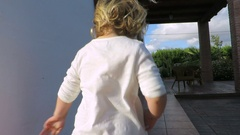 Back blonde baby running exterior to door house Stock Footage