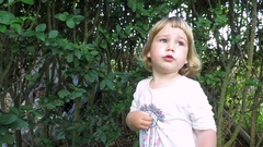 Cute blonde baby two years talking in garden Arkistovideo