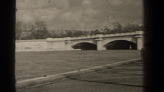 1947: a panning view of a river flowing under a bridge and near some buildings Stock Footage