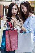 Two beautiful asian shopaholic women with smartphone and colorful shopping .. Stock Photos