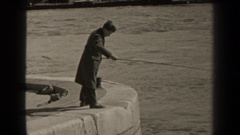 1947: a man with a fishing pole standing on a cement platform adjacent  Stock Footage