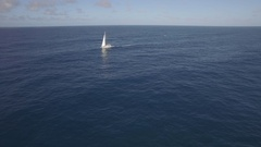 Aerial view of sailing white yacht in empty ocean blue water against clear sky Stock Footage
