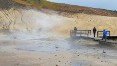 Tourists are strolling on geothermal area Seltun in Iceland, white steam is Stock Footage