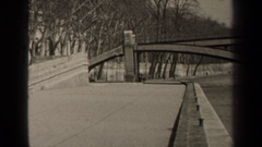 1947: metal arches supports horizontal span across river between pathway  Stock Footage