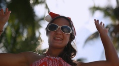 Happy young woman in sunglasses and christmas hat enjoying the sun in tropical Stock Footage