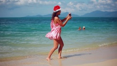 Christmas young smiling woman in red santa hat and sunglasses taking picture Stock Footage
