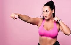 Plump concentrated woman doing sport exercises Stock Photos