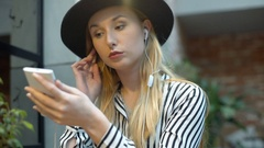 Elegant woman listening music in the cafe and looking morose Stock Footage
