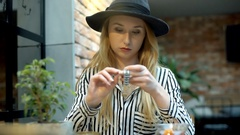 Elegant woman sitting in the cafe and tries to set time on her silver watch Stock Footage