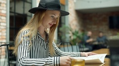 Elegant woman in black hat sitting in the cafe and reading menu Stock Footage