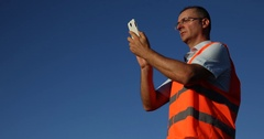 Airport Staff Ground Service Man Using a Mobile Phone Aircraft Passing Overhead Stock Footage