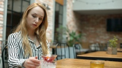 Woman looks pensive while sitting in the cafe and drinking fancy beverage Stock Footage
