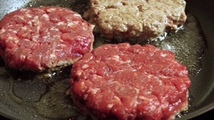 Cooking hamburger. Three beef cutlets for burgers are fried in a frying pan. HD Stock Footage