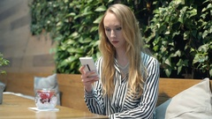 Irritated woman waiting for someone in the outdoor cafe and checking time Stock Footage