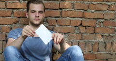 Unhappy Boy Sad Man Reading Bad News Paper Letter Legal Citation Red Bricks Wall Stock Footage