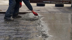 Leveling Wet Concrete Surface with a Metal Screed Board Stock Footage