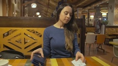 Brunette woman pays for tea in the cafe getting cash from purse Stock Footage