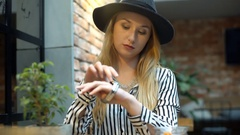 Elegant woman sitting in the cafe and looking at her silver watch Stock Footage
