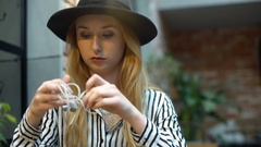 Elegant woman sitting in the cafe and trying to untangle earphones Stock Footage